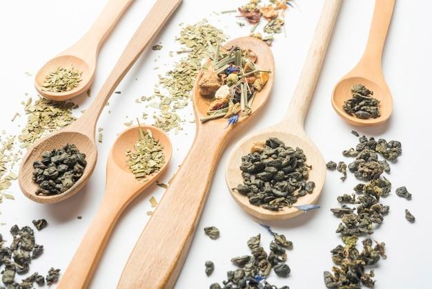 Vários tipos de chá de ervas em colheres de madeira no fundo branco