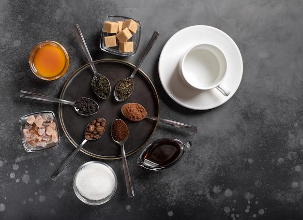Vários tipos de chá (preto, verde, ervas), café (moído, feijão, cacau), adoçantes e uma superfície escura de xícara vazia branca, vista superior