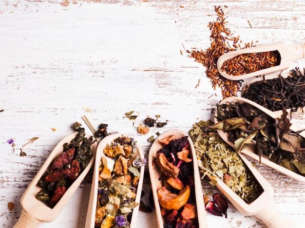 Vários tipos de chá seco em colheres de madeira na mesa branca surrada