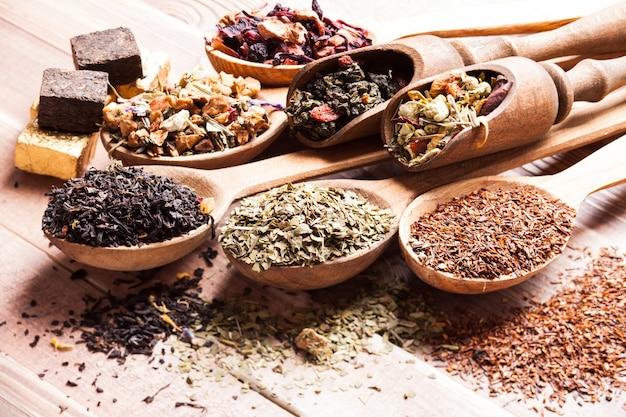 Vários tipos de chá seco em colheres e colheres de madeira