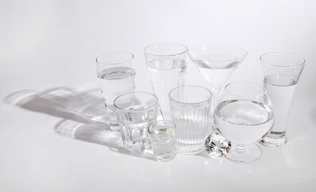 Vários tipos de copos com água pura, isolado no fundo branco