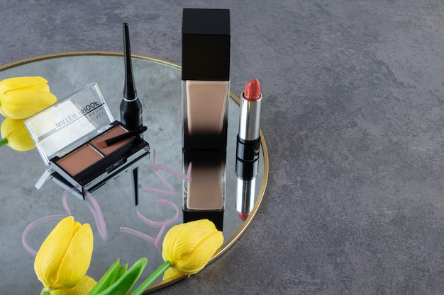 Vários tipos de cosméticos no espelho sobre fundo cinza.