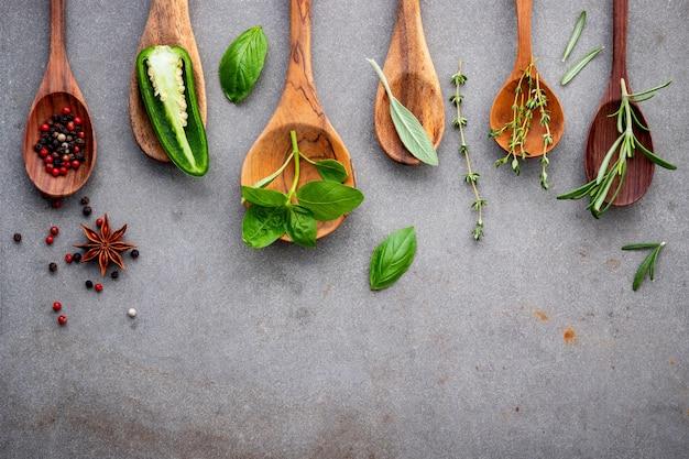 Vários tipos de especiarias e ervas em colheres de madeira.