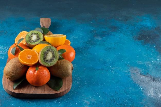 Vários tipos de frutas frescas colocadas em uma tábua de madeira