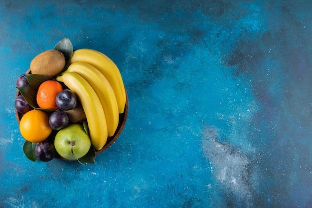Vários tipos de frutas frescas colocadas em uma tigela de madeira