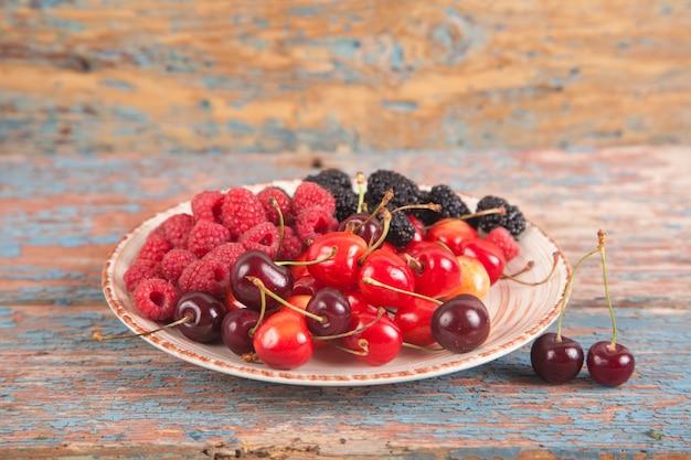 Vários tipos de frutas suculentas maduras em um prato. fundo de madeira framboesa, cereja, amora