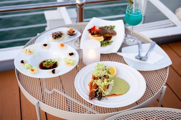 Vários tipos de frutos do mar em chapa branca com coquetel azul na mesa no pátio do telhado do navio