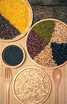 Vários tipos de grãos de cereais, tipos de feijão e ervilha em fundo de madeira.