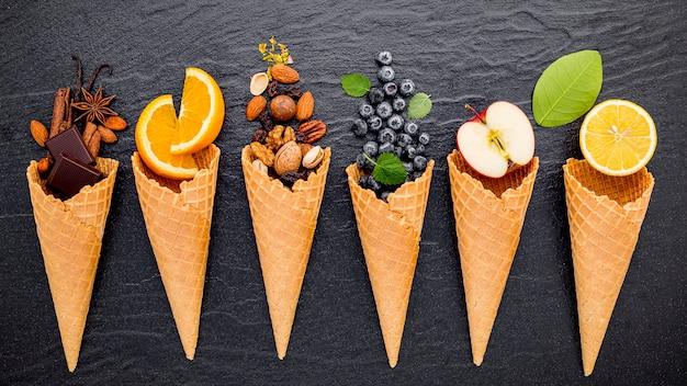 Vários tipos de ingredientes para sorvetes em cones criados em pedra escura