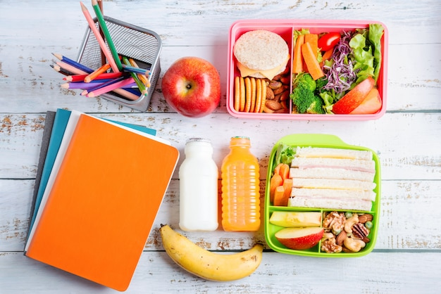 Vários tipos de lancheiras saudáveis de sanduíche. kid bento pack para escola conjunto em pacote plástico, banana e maçã com suco de laranja, leite.