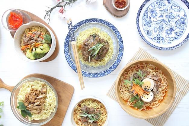 Vários tipos de macarrão e ramen com brócolis de ovo e carne na mesa branca