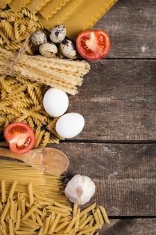Vários tipos de macarrão seco com tomates na madeira