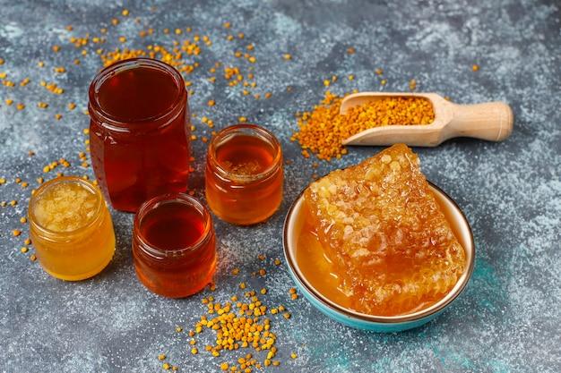Vários tipos de mel em potes de vidro, favos de mel e pólen