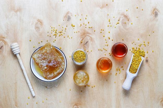 Vários tipos de mel em potes de vidro, favos de mel e pólen.