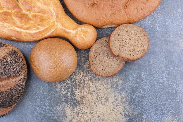 Vários tipos de pães se agrupam na superfície de mármore