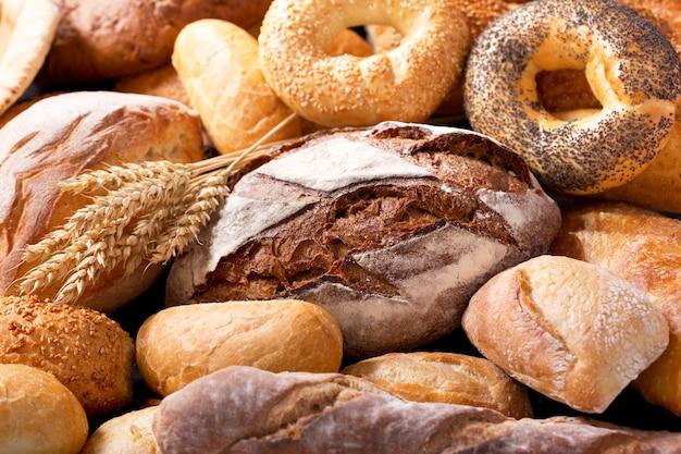 Vários tipos de pão fresco com espigas de trigo como pano de fundo