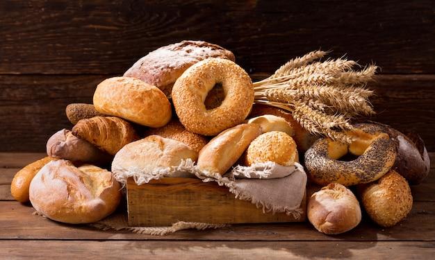 Vários tipos de pão fresco com espigas de trigo na mesa de madeira