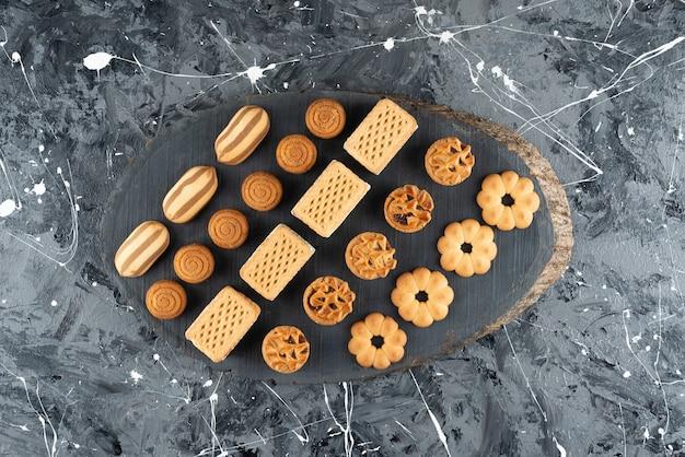 Vários tipos de pastéis doces em uma peça de madeira