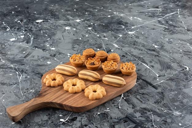 Vários tipos de pastéis doces em uma tábua de madeira