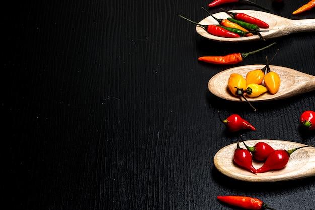 Vários tipos de pimentas em colheres de madeira em um fundo preto de madeira rústico. vista superior copiar espaço