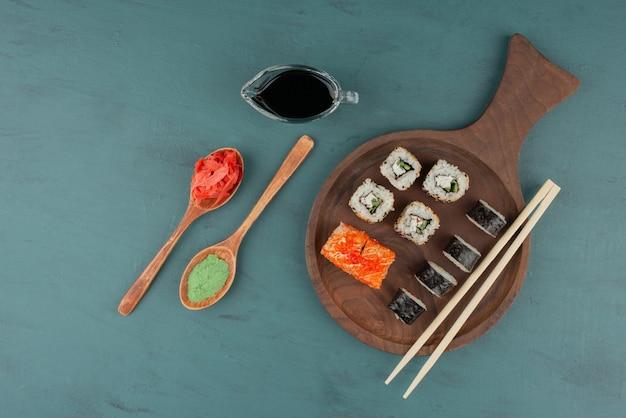 Vários tipos de prato de rolo de sushi com gengibre em conserva, wasabi e molho de soja na mesa azul.