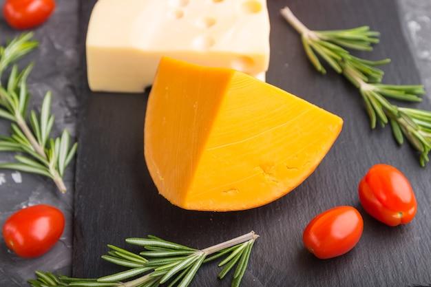 Vários tipos de queijo com alecrim e tomate em uma placa de ardósia preta em uma superfície de concreto preto