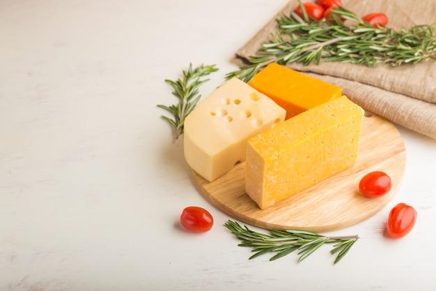 Vários tipos de queijo com alecrim e tomate na placa de madeira sobre uma superfície de madeira branca e tecido de linho
