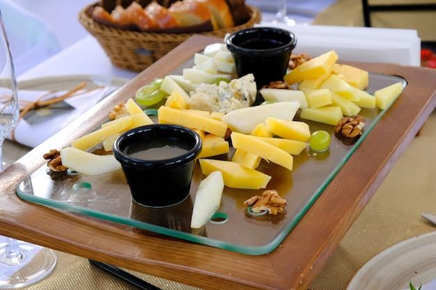 Vários tipos de queijo cutted em uma bandeja de madeira em uma mesa de banquete em um restaurante.