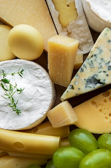 Vários tipos de queijo, manjericão e uvas na mesa