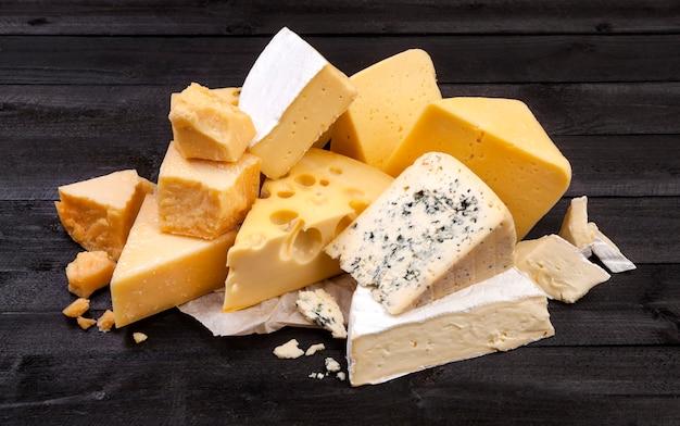 Vários tipos de queijo na mesa de madeira preta.