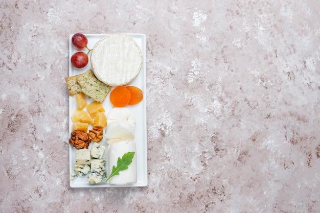 Vários tipos de queijo na superfície marrom clara