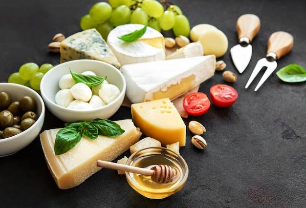 Vários tipos de queijo, uva, mel e salgadinhos em uma superfície de concreto preto