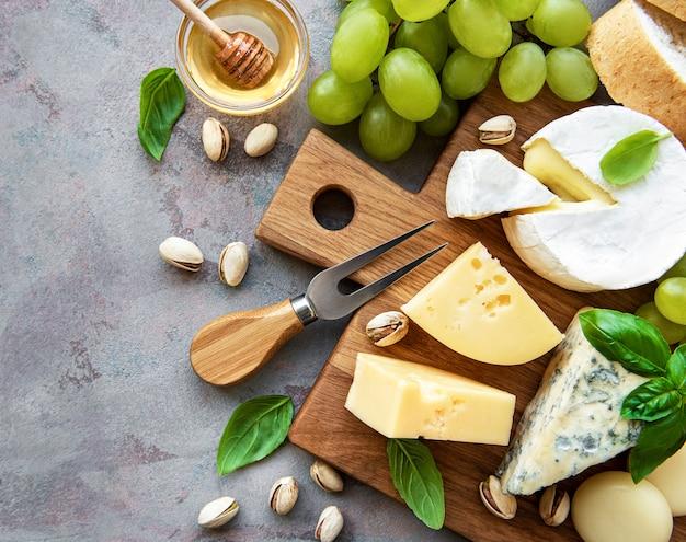 Vários tipos de queijo, uvas e salgadinhos em uma superfície de concreto cinza