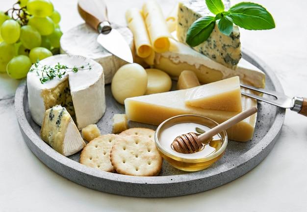 Vários tipos de queijos, uvas e mel em uma mesa de mármore