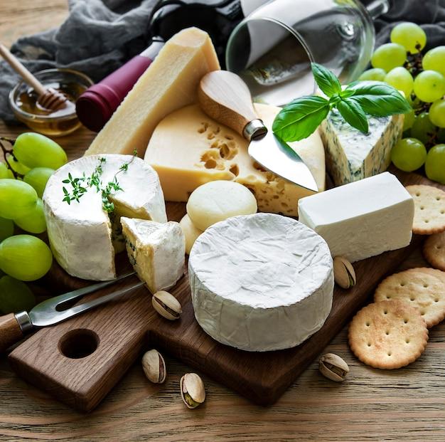 Vários tipos de queijos, uvas e vinhos em uma mesa de madeira