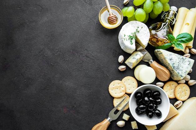 Vários tipos de queijos, uvas, mel e salgadinhos