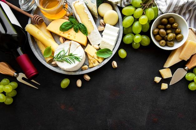 Vários tipos de queijos, uvas, vinhos e salgadinhos em uma mesa de concreto preto