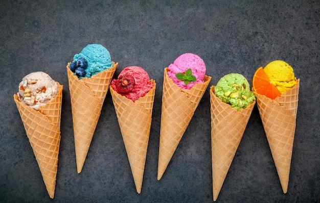 Vários tipos de sabor de sorvete em cones configurados em fundo de pedra escura.