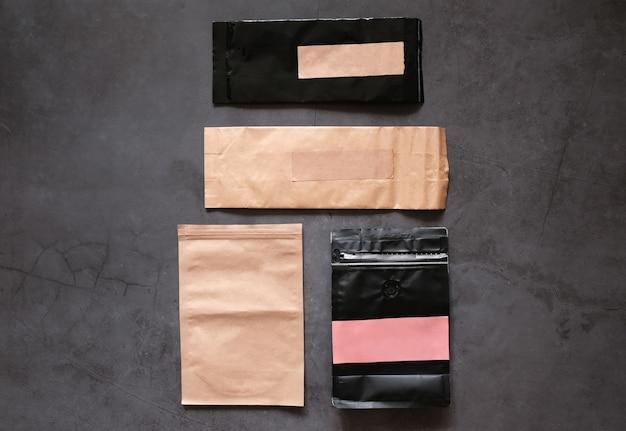 Vários tipos de saco de grãos de café em branco simulado de marca em fundo de ardósia de pedra escura, conceito de comida e bebida