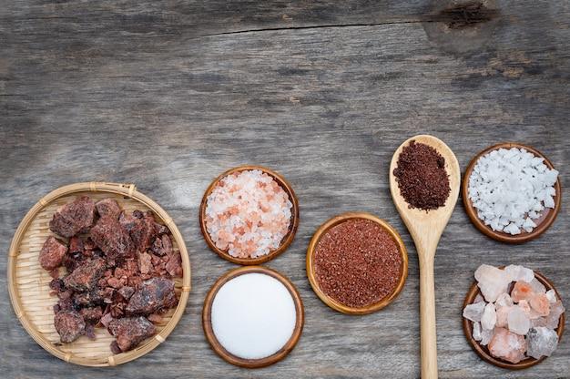 Vários tipos de sal em tigelas no fundo de madeira