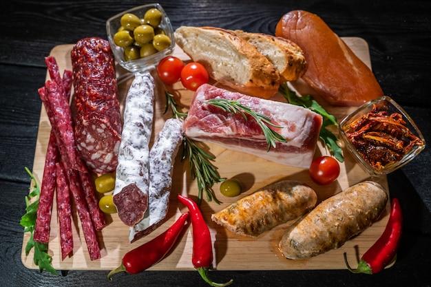 Vários tipos de salame, grão e salsichas em uma mesa de madeira