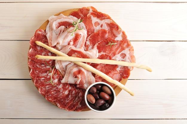 Vários tipos de salsichas fatiadas com salame, bacon, presunto