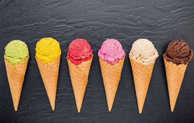 Vários tipos de sorvete em cones criados em pedra escura