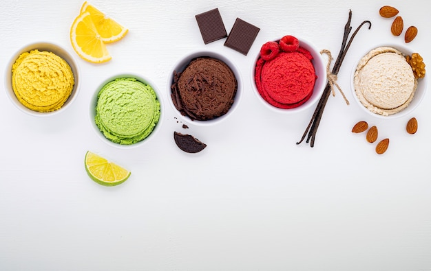 Vários tipos de sorvete sabor bola mirtilo, limão, pistache, amêndoa, laranja, chocolate e baunilha configurados em fundo branco de madeira. verão e conceito de menu doce.