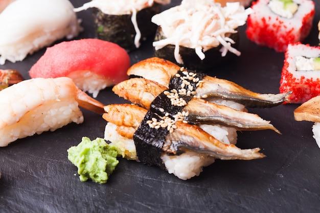 Vários tipos de sushi e wasabi na bandeja de ardósia