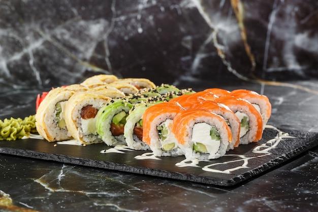 Vários tipos de sushi serviram em fundo de mármore preto. menu de sushi para comida japonesa. conjunto de sushi japonês. pãezinhos com atum, salmão, camarão, caranguejo, caviar e abacate. foto horizontal.