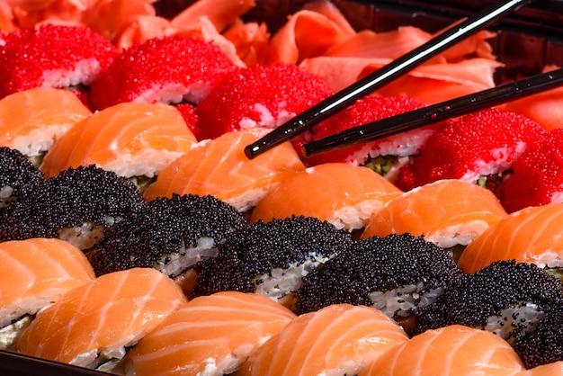 Vários tipos de sushi serviram em um escuro. rolo com salmão, abacate, pepino. menu de sushi. comida japonesa