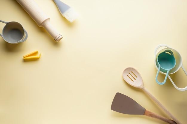 Vários utensílios de cozinha em um fundo amarelo, com lugar para texto. postura plana.