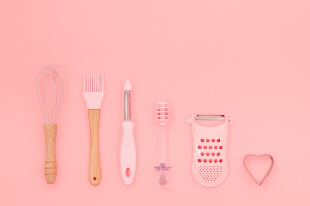Vários utensílios de cozinha rosa sobre fundo rosa abstrato. forma de cozimento maior, bata e ferro. vista horizontal superior copyspace amor conceito cookong