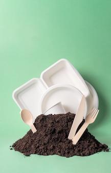 Vários utensílios de mesa de uso único, alternativas populares de não plástico, monte no solo no verde